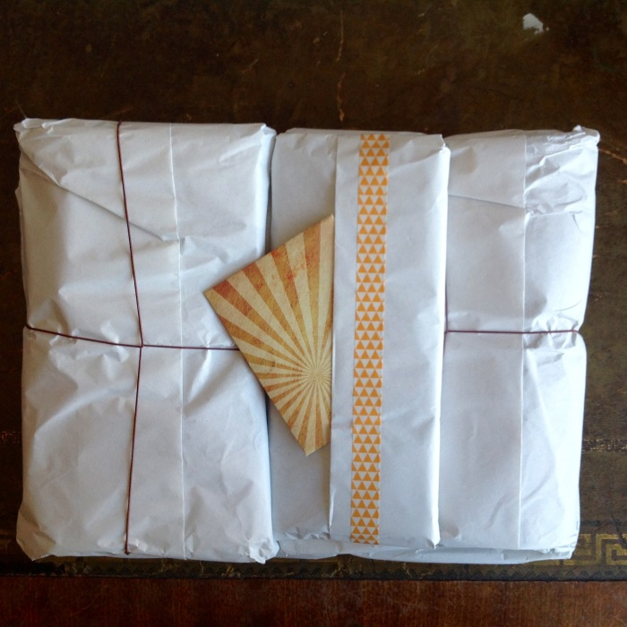 Four little parcels all individually wrapped with a card.